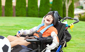Child smiling in a wheelchair