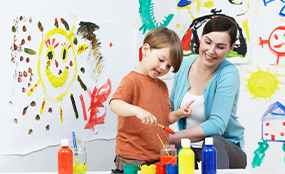 Child painting with teacher