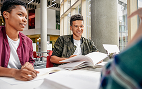 Three teenagers sat at a desk with open books